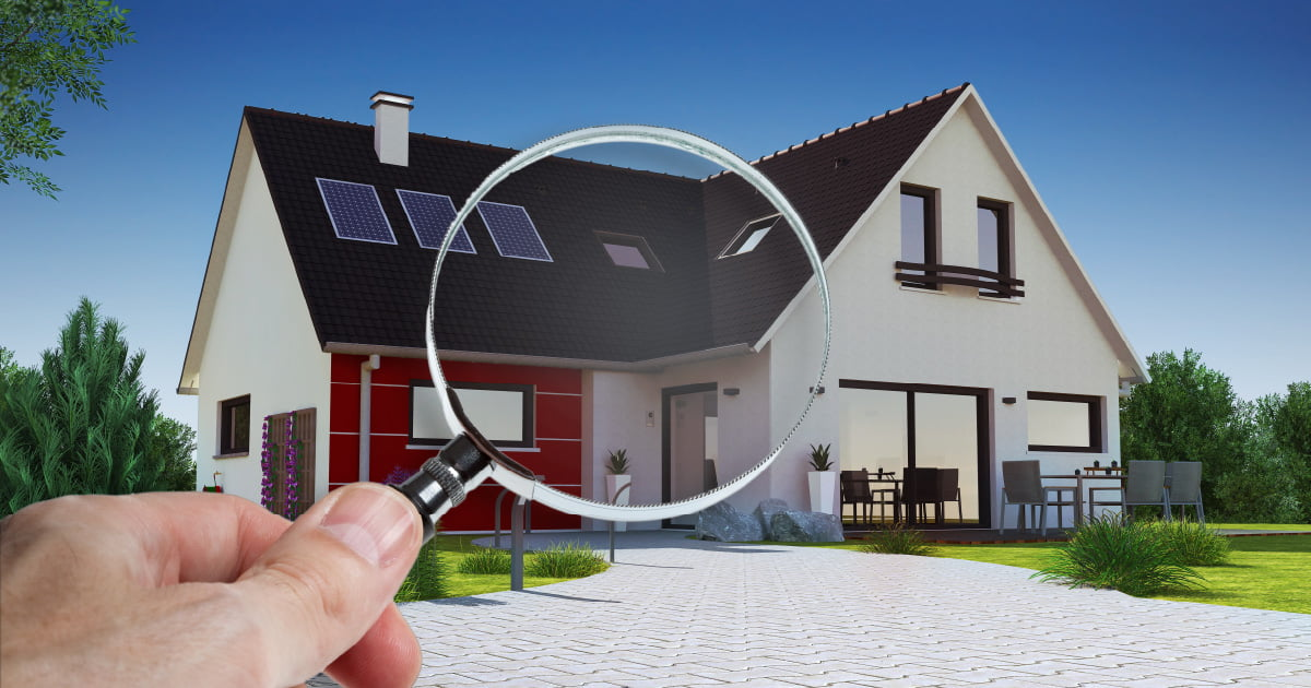 A hand holding a magnifying glass in front of a house signifying the house is being looked at for a housing inspection.