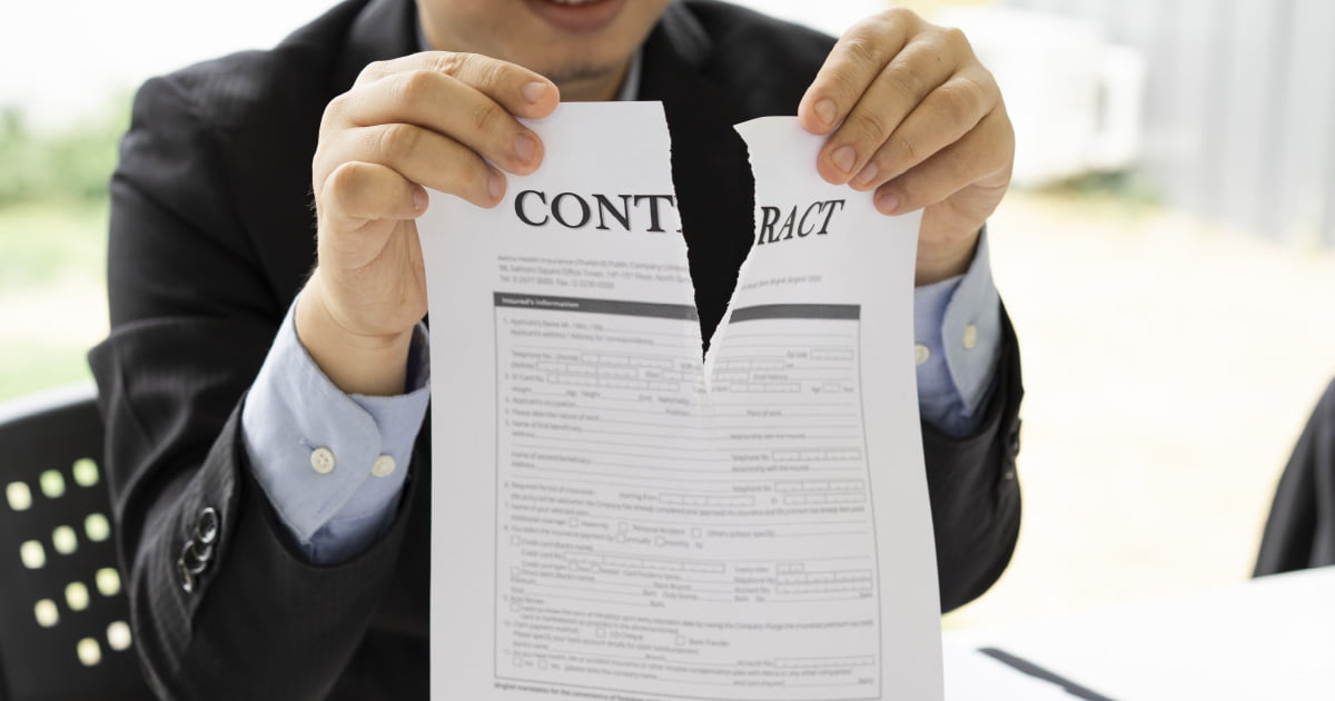 An agent is tearing up a piece of paper indicating the termination of a new loan contract.