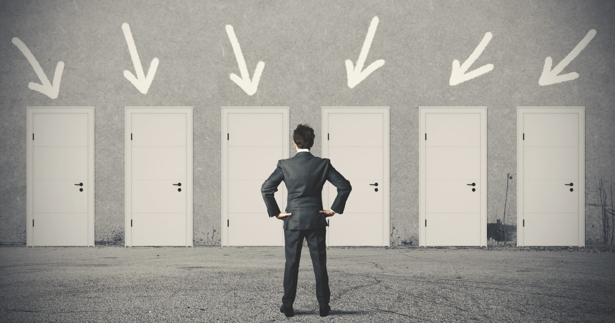 A man staring at a group of doors indicating he is considering the proper offer to submit to buy a luxury home.